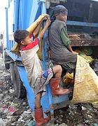 Bambini raccolgono immondizia a Manila (foto Epa)
