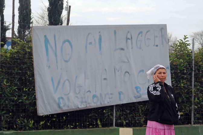 Rivolta al campo rom: in via Salone i nomadi bloccano il trasferimento di 120 persone, poi intorno alle 13 l'accordo. Un cartello contesta il campo per rifugiati di Castelnuovo (foto Mario Proto)