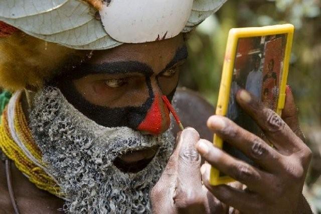 TIM LAMAN. «Il trucco». Un uomo con vestiti tradizionali da cerimonia si dipinge il viso. Papua Nuova Guinea