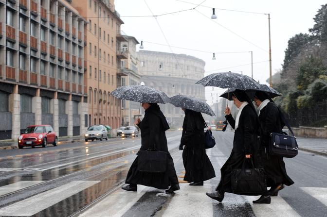 Nevicata su Roma: religiose sotto la neve vicino al Closseo, i cui cancelli sono stati chiusi. I turisti sono stati evacuati dall'anfiteatro intorno alle 11 per motivi di sicurezza (foto Jpeg)