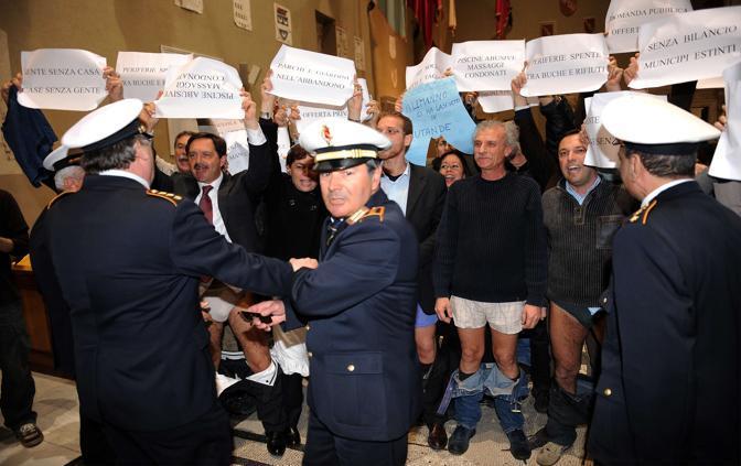 L'intervento dei vigili urbani per interrompere la protesta «in mutande» (Afp)