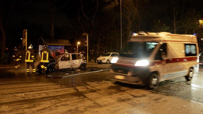 Gli scontri fuori dallo stadio subito dopo il derby Lazio-Roma vinto dai giallorossi: un'ambulanza passa accanto all'auto bruciata   (Ansa)