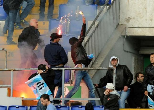 Tifosi lanciano i pedardi sugli spalti subito dopo la fine del derby (Foto Afp)