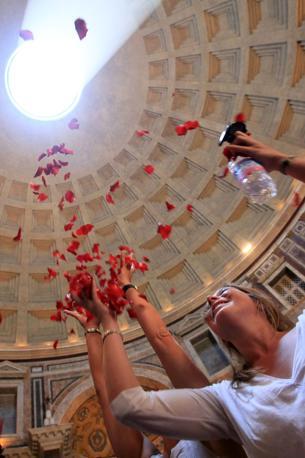 Turisti raccolgono al volo i petali rossi che cadono dall'apertura sovrastante il Pantheon, a 43 metri d'altezza. E' la pioggia di rose, cerimonia che ebbe origine con i primi cristiani giunti a Roma (foto Eidon)