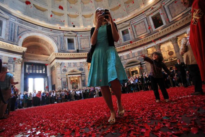Il pavimento coperto di petali rossi che cadono dall'apertura sovrastante il Pantheon, a 43 metri d'altezza. E' la pioggia di rose, cerimonia che ebbe origine con i primi cristiani giunti a Roma (foto Eidon)
