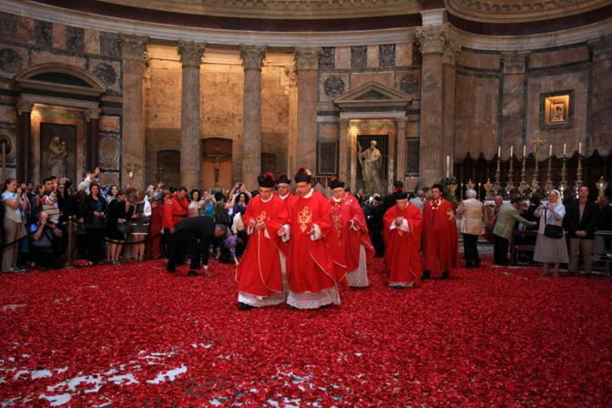 Sacerdoti e alti prelati camminano sul tappeto di petali rossi caduti dall'apertura sovrastante il Pantheon, a 43 metri d'altezza. E' la pioggia di rose, cerimonia che ebbe origine con i primi cristiani giunti a Roma (foto Eidon)
