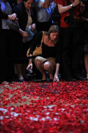 Una turista raccoglie i petali rossi che cadono dall'apertura sovrastante il Pantheon, a 43 metri d'altezza. E' la pioggia di rose, cerimonia che ebbe origine con i primi cristiani giunti a Roma (foto Eidon)