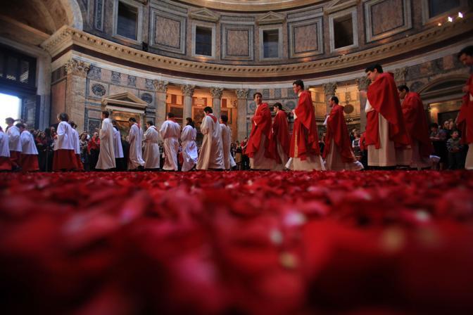 Chierichetti e sacerdoti camminano sui petali rossi nel Pantheon, dopo la pioggia di rose, cerimonia che ebbe origine con i primi cristiani giunti a Roma (foto Eidon)