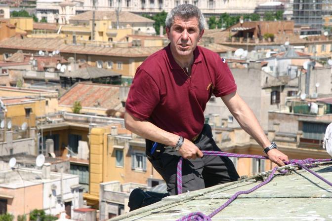 Pioggia di rose dall'«occhio del cielo» nel Pantheon di Roma: uno dei vigili del fuoco in cordata sul tetto del monumento per lanciare i petali (foto Comando Vigili del Fuoco Roma)