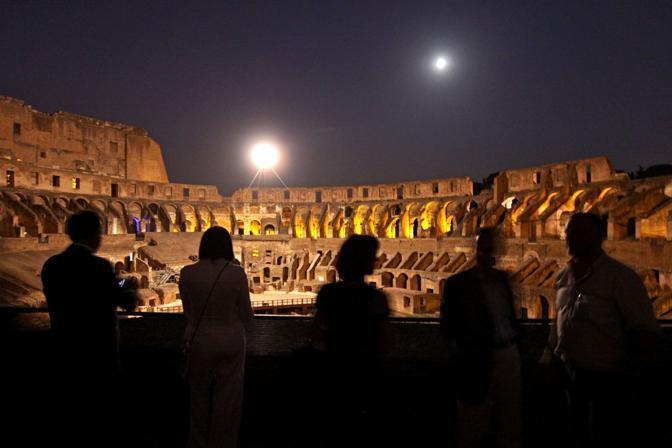 Turisti ammirano le due lune al Colosseo: in alto a destra la Luna, a sinistra il globo splendente della mongolfiera, la luna artificiale che rischiara l'arena dei gladiatori. Sabato 21 agosto sono riprese le visite guidate notturne dell'Anfiteatro Flavio a Roma (foto Jpeg)