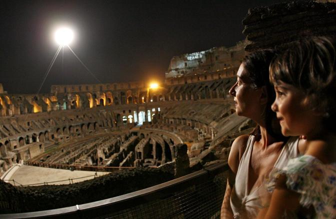Turisti ammirano il globo splendente della mongolfiera, la luna artificiale che rischiara l'arena dei gladiatori al Colosseo. Sabato 21 agosto sono riprese le visite guidate notturne dell'Anfiteatro Flavio a Roma (foto Jpeg)
