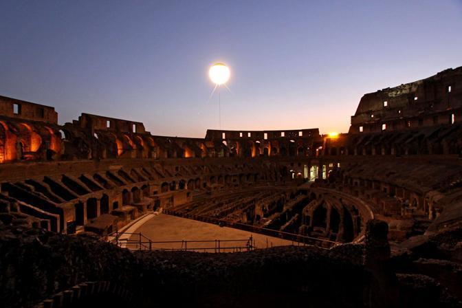 Tramonto con luna artificiale: il globo splendente è una mongolfiera che rischiara l'arena dei gladiatori al Colosseo. Sabato 21 agosto sono riprese le visite guidate notturne dell'Anfiteatro Flavio a Roma (foto Jpeg)