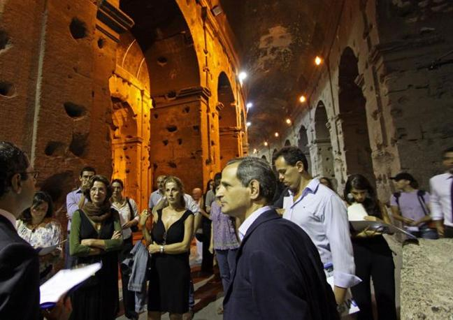 Turisti al Colosseo con il sottosegretario ai Beni Culturali Francesco Giro (in primo piano con giacca blu), che ha inaugurato a prima delle visite guidate notturne dell'Anfiteatro Flavio, riprese sabato 21 agosto a Roma (foto Jpeg)