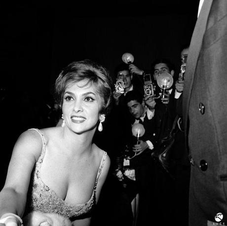 1960, Roma. I fotografi fanno ressa intorno a Gina Lollobrigida, ritratta in occasione della prima del film Ben Hur. Diva per bravura, bellezza e carattere, dai primi anni cinquanta sarà protagonista assoluta dello star system internazionale e delle cronache mondane.