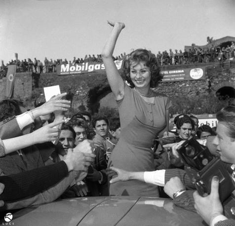 1956, Roma. Sophia Loren alla partenza del III Rallye del Cinema. Nata nel 1953, la manifestazione – organizzata da Ezio Radaelli - avrà un suo ruolo nella costruzione del divismo popolare, portando attori, attrici e registi a ricevere bagni di folla nelle tappe toccate tra Roma e Sanremo dalla kermesse motoristica. L'attrice, pari merito con Alberto Sordi, aveva vinto l'edizione dell'anno precedente