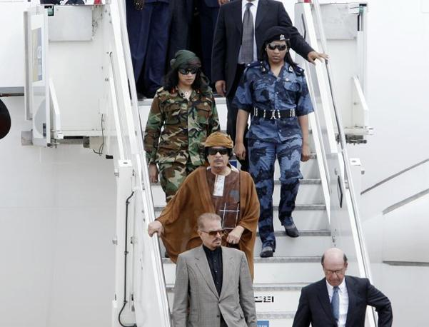 Il leader libico Muammar Gheddafi, a Ciampino scende dal suo aereo scortato come di consueto, da due «amazzoni» in tuta mimetica che lo seguono in ogni suo spostamento (foto Blowup)