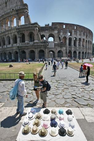 Ambulanti e camion bar padroni del centro storico. Qui sopra, venditore di cappelli abusivo al Colosseo. Tra irregolari e postazioni munite di permessi, l'occupazione del suolo pubblico nell'area dall'Arco di Costantino a piazza venezia è divenuta un'invasione: un rivenditore ogni 25 metri (foto Jpeg)