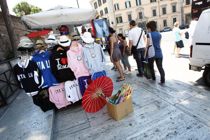 Ambulanti e camion bar padroni del centro storico. Qui sopra, un ambulante vende magliette a due passi dalla scalinata del Campidoglio (foto Jpeg)