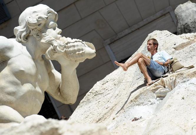 Relax sulla fontana di Trevi. Un giovane turista italiano si è arrampicato la domenica di Ferragosto sui massi che affiancano le sculture di Fontana di Trevi. E qui ha consumato un picinic improvvisato mettendosi poi a leggere. I vigili del fuoco lo hanno infine convinto a scendere (foto Ansa/Ferrari)