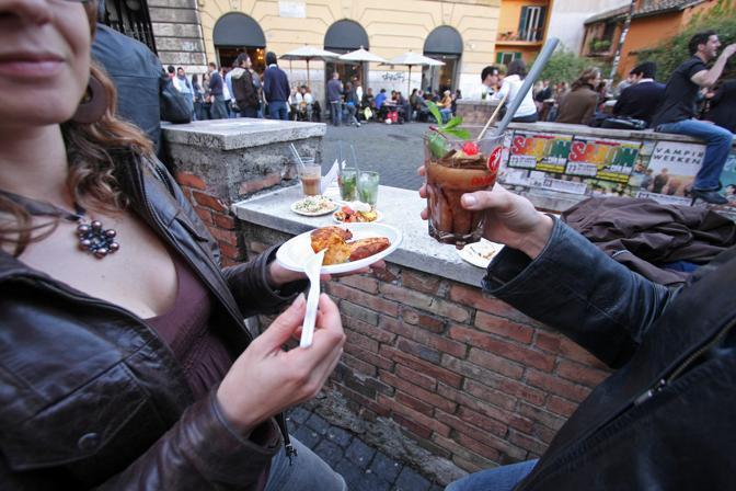 «36 hours in Rome», le tappe dell'itinerario suggerito dal New York Times nella Città Eterna: sopra, ragazzi all'aperitivo da «freni e Frizioni» a Trastevere (foto Jpeg)