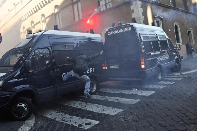 Studenti in piazza contro il governo: scontri e tafferugli. Un dimostranti prende a calci una camionetta dei carabinieri (Lapresse)