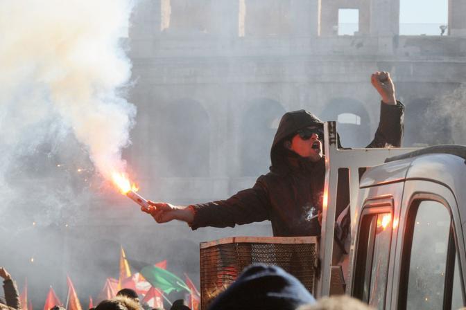 Studenti in piazza contro il governo: scontri e tafferugli. Un dimostrante accende un fumogeno alla testa del corteo dei Fori Imperiali (Eidon)