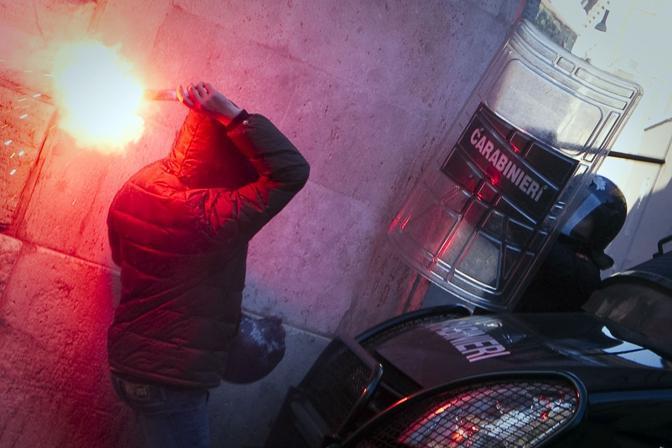 Studenti in piazza contro il governo: scontri e tafferugli. Un dimostrante affronta i carabinieri armato di un fumogeno (Lapresse)