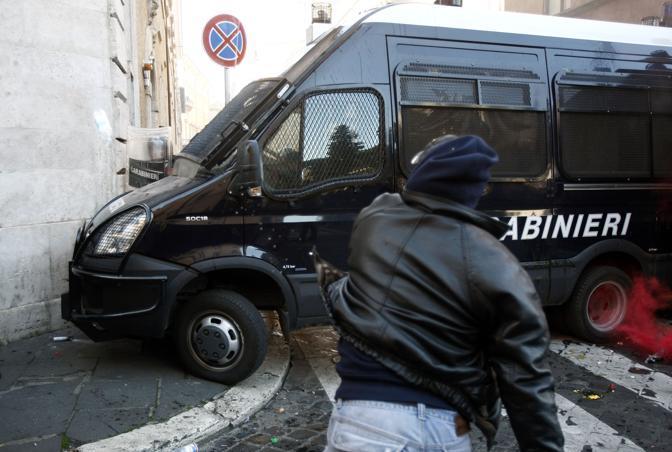 Studenti in piazza contro il governo: scontri e tafferugli. Un dimostrante lancia oggetti contro una camionetta dei carabinieri (Lapresse)