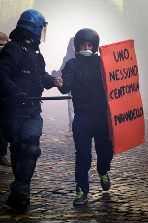 Studenti in piazza. Un ragazzo con uno scudo-libro fermato dalla Polizia (Lapresse)
