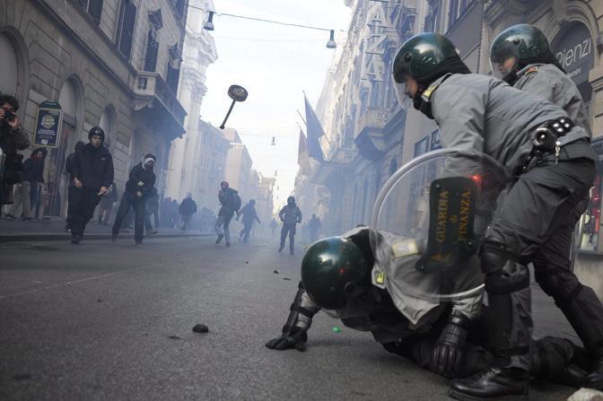 Studenti in piazza contro il governo: scontri e tafferugli. Un agente delle Fiamme Gialle a terra dopo essere stato colpito da un oggetto lanciato dai manifestanti (Ansa)