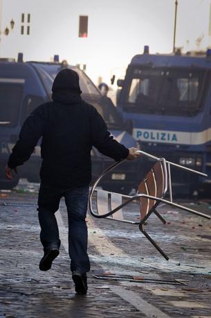 Studenti in piazza contro il governo: scontri e tafferugli. Un manifestante con una sedia (Lapresse)