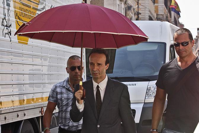 Per proteggersi dal sole, Benigni - in giacca e cravatta scuri - usa un ombrello rosso (Jpeg)