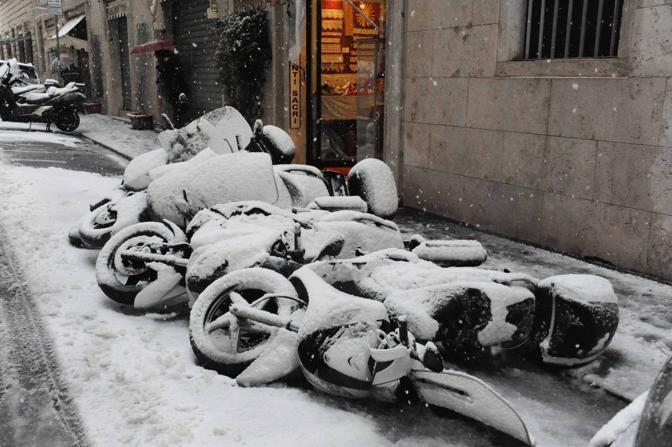 Motorini buttati a terra da un automobilista e coperti da neve in centro a Roma (foto Proto)