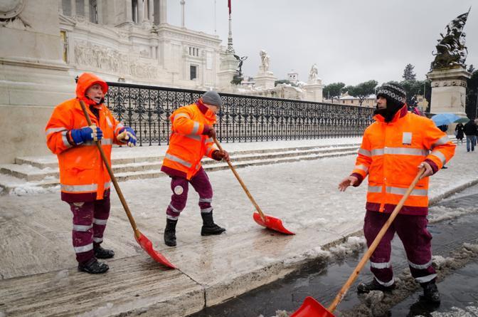 Addetti dell'Ama puliscono i marciapiedi davanti al Vittoriano: il rischio di cadute causa neve e ghiaccio è alto (Milestone)