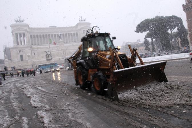 Una ruspa rimuove la neve in via dei Fori Imperiali: con l'abbassamento delle temperature le strade potrebbero diventare piste di ghiaccio (Insidefoto)