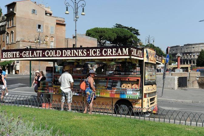 Turisti acquistano bevande da un camion-bar in via dei Fori imperiali (foto Jpeg)