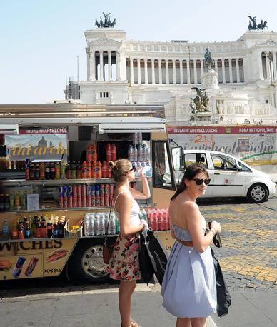 Una turista si disseta dopo aver acquistato una bottiglietta davanti al Vittoriano (foto Jpeg)