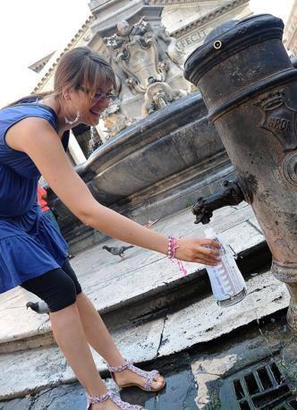 Una turista usa l'Eco-water per bere da una fontanella, davanti al Pantheon (foto Jpeg)