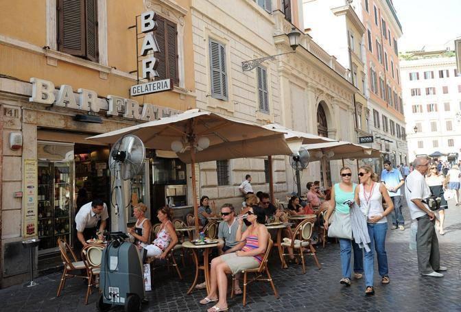 Gruppi di turisti seduti ai tavolini del Bar Frattina, in via Frattina (foto Jpeg)