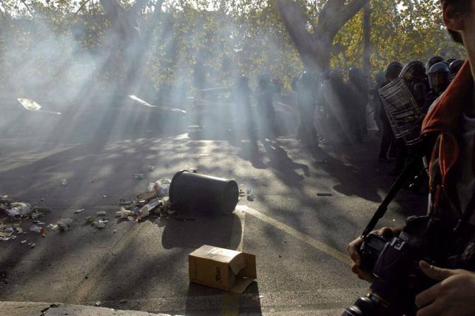 Bidoni, tavolini, sassi: la polizia cammina tra gli oggetti lanciati dai dimostranti (Carofei)