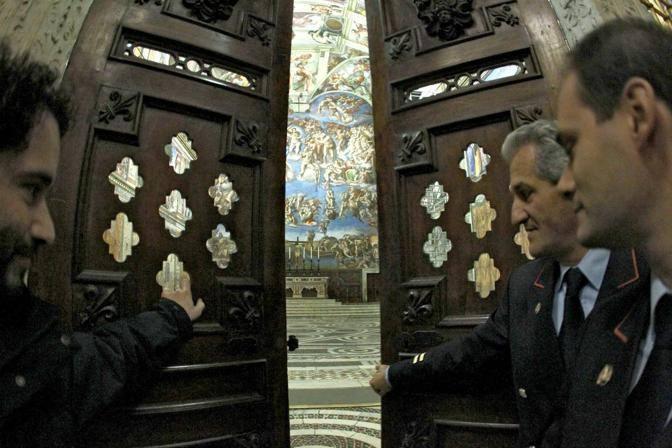 I dipendenti dei Musei Vaticani aprono le porte della Cappella Sistina: si intravedono gli affreschi di Michelangelo (foto Benvegnù-Guaitoli © Musei Vaticani - Tutti i diritti riservati)
