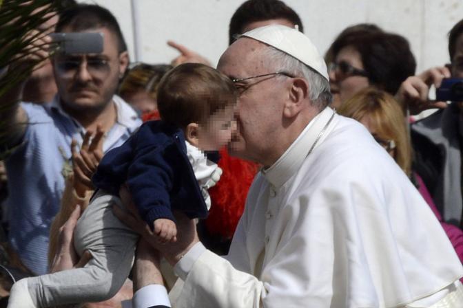 Papa Francesco bacia un piccolo fedele (Afp)
