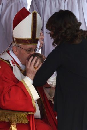 Il bacio a un neonato durante la celebrazione della Messa (Afp)