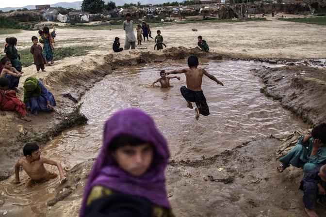 La vita quotidiani di alcuni bambini rifugiati in Pakistan: bagni e giochi nell'acqua piena di fango creata da un gettito nel campo di Islamabad (AP Photo/Muhammed Muheisen)
