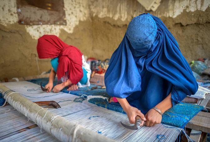 Alcune donne afghane in un campo profughi vicino Peshawar mentre lavorano un tappeto  (Afp Photo/A MAJEED)