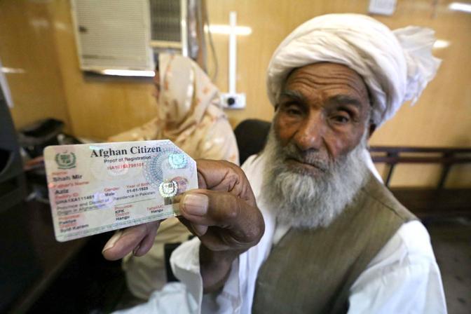 Un profugo afghano mostra il documento di identità mentre si prepara a lasciare un campo profughi per l'Afghanistan al centro di registrazione dell'Unhcr di Chamkani a Peshawar (Foto Epa)