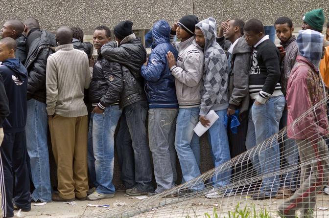 Centinaia di rifugiati africani il 20 giugno a Cape Town in fila per chiedere il prolungamento del diritto di asilo (Afp photo)