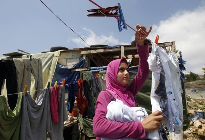 Una donna siriana rifugiata stende i panni davanta alla sua baracca a Alman in Libano (Reuters)