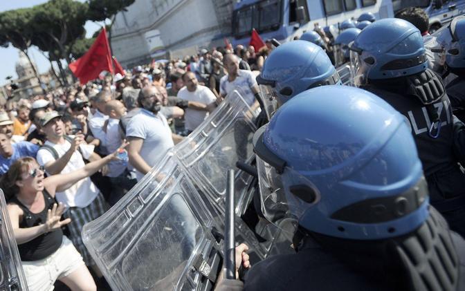 La ragazza con la canottiera nera, a sinistra nella foto, si fa avanti per chiedere ai poliziotti di   stare calmi (Foto Jpeg)