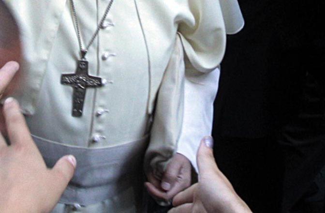 Bergoglio è arrivato in chiesa con la sua mitria nella mano sinistra. L'ha poi indossata prima all'ingresso e poi in altri momenti della liturgia (Foto Jpeg)